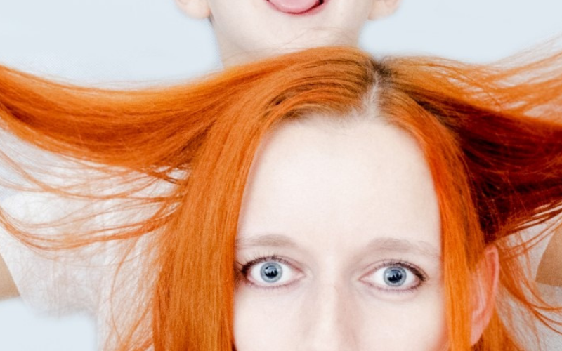 Bewildered mama with child on top being silly